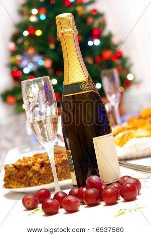 Geriffelter, Glas und Flasche Champagner in Tabellenform Weihnachten feiern mit Essen
