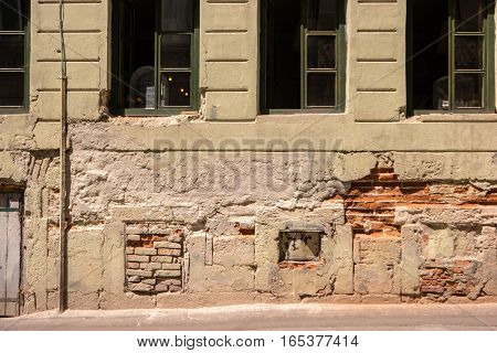 Damaged wall with windows. Bricks and old cement. Wander around the historic district.