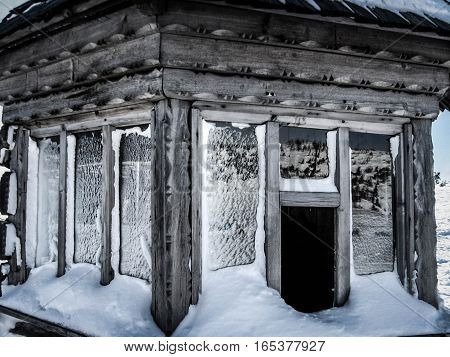 Snow-covered windows a small wooden house facade made from wood carving