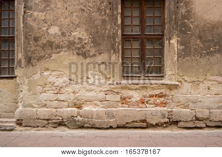 Window and damaged wall. Cracked paint and bricks. History of old streets.