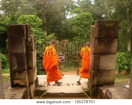SIEM REAP, CAMBODIA - AUGUST 06, 2014 - Unidentified young buddhist monks inside the ruins of Baphuon temple