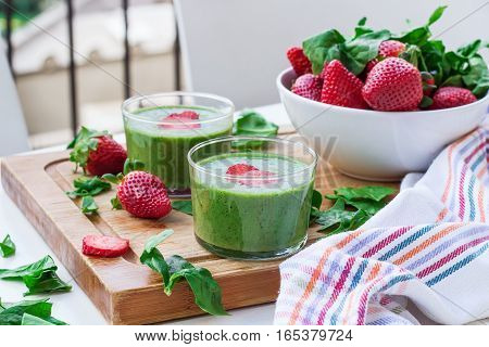 Green spinach smoothie in a glass with strawberry on a wooden cutting board. Outdoor summer composition, selective focus