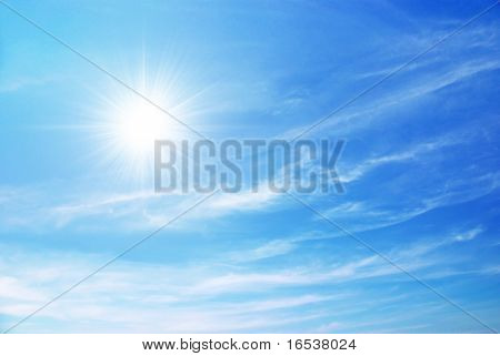 bright blue sky with sun shining and some clouds