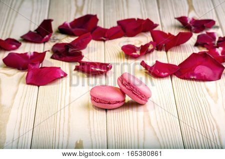 Macaroons with red rose petals on wooden background
