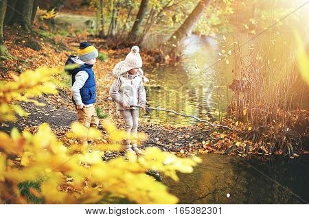 Two Kids With Branch Near The Pond