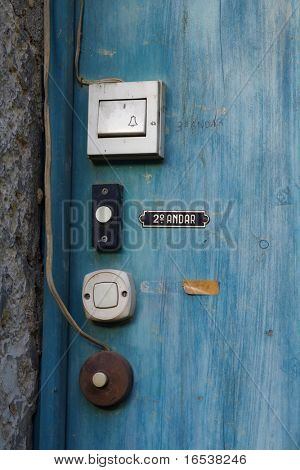Old white door bells in a blue wooden door