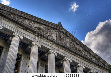 A high dynamic range image of the sculpture and quote of Into the Highlands of the Mind let me go on the Sacramento Library and Courts building with a blue sky and white clouds