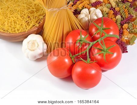 Ripe Tomatoes Branch, Uncooked Italian Pasta And Garlic On A White