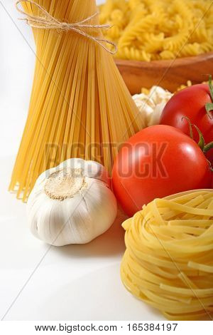 Ripe Tomatoes, Uncooked Italian Pasta And Garlic On A White
