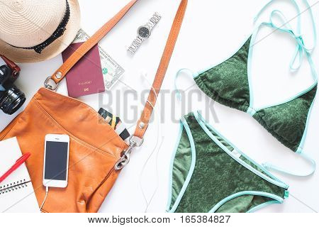 Set of summer holiday items. Green color bikini with mobile phone leather bag camera and passport for summer vacation on white background