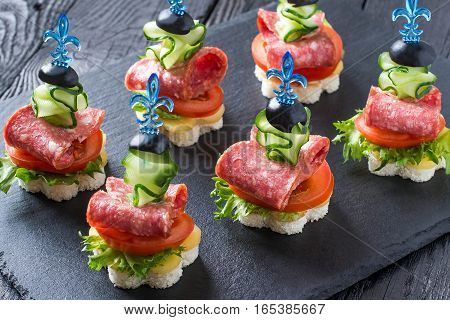 Colorful canape on skewers with vegetables and sausage on a slate plate. Tasty appetizer for a party or banquet