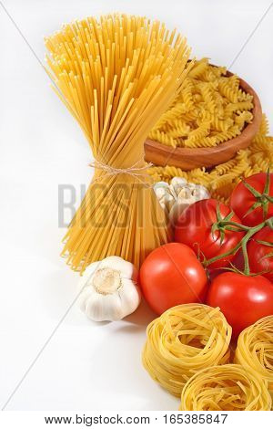 Uncooked Italian Pasta, Ripe Tomatoes Branch And Garlic On A White