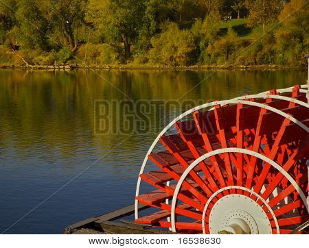 red river boat paddle wheel in water with trees