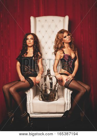 Two young sexy women in lingerie on white throne