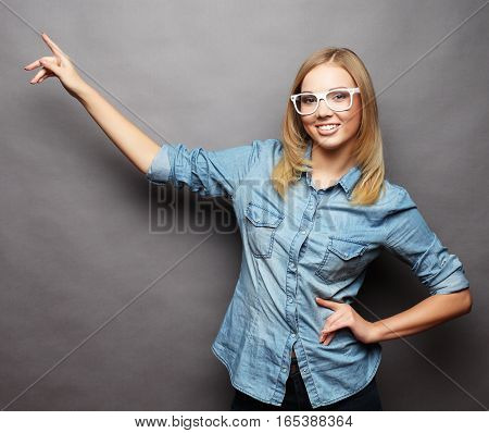 Happy smiling beautiful young woman showing copyspace, visual imaginary or something, or pressing virual button over grey background