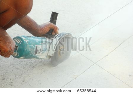 Worker use grinding machine cutting concrete floor