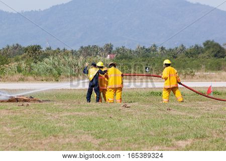 Firefighter in action spraying fire with fire hose