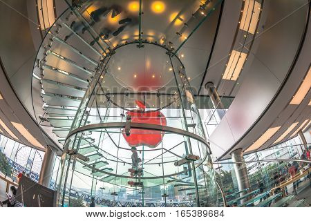 Hong Kong, China - December 4, 2016: fish-eye ground view of red Apple sign and glass spiral stairway in Apple store, IFC Mall, with Hong Kong Central District skyline on background.