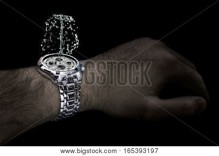 Silver watch with fountain on the wrist of man. Isolated on the black background.