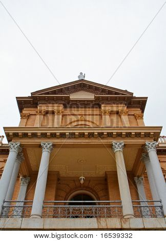 Front facade of pillared tan brick courthouse with statue on top