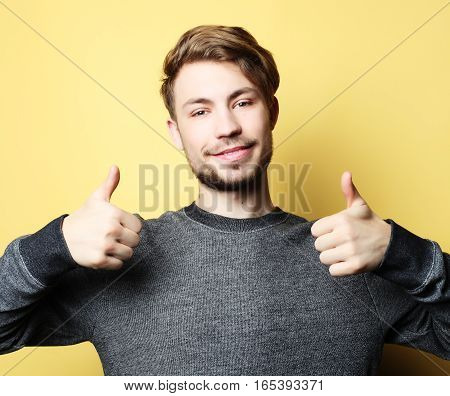 Happy handsome man showing thumbs up over yellow background
