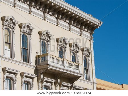 1800s gold country tan ornate building face with balcony and blue sky