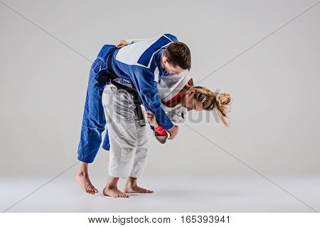 The two judokas fighters - man and woman - posing on gray studio background