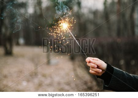 A girl holds a sparkler in hand