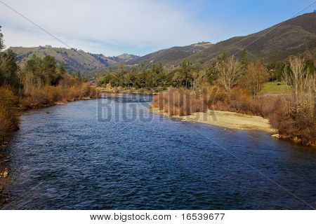 Curving blue water of the coloma river with green hills and blue sky background