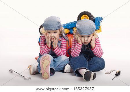 two cute little twin girls repairing car