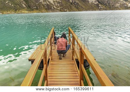QUILOTOA, ECUADOR, FEBRAURY - 2016 - People at wooden breakwater at Quilotoa lake Latacunga Ecuador
