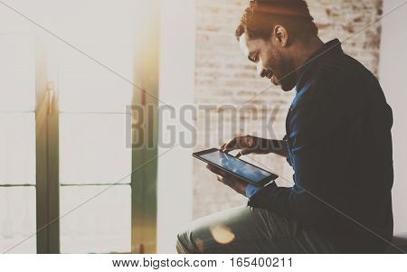 Musing young African American freelancer touching display of digital tablet while working in new project at home. Black businessman looking for information on Internet. Blurred, color filter, flares.