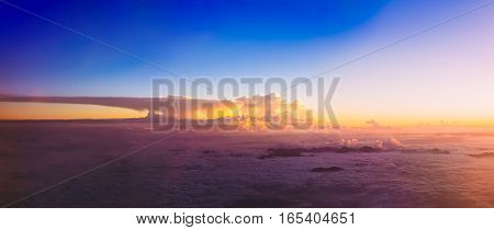 Beautiful panorama of sunset over mountains from height of airplane. Bright Blue, Orange, Yellow and Purple Colors of Sunrise Sky.