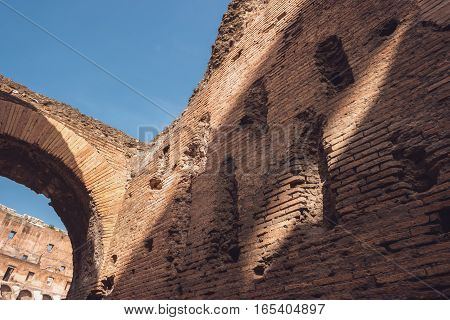 Damaged brick wall and arch. Ruins and blue sky. Remnants of old world.