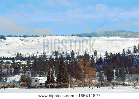 Scenic winter landscape view with snow covered hills behind houses and trees. Bright blue sky and scattered grey clouds background.