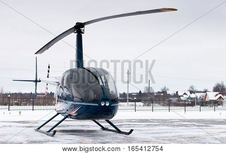 Small private helicopter. Blue helicopter on snowy heliport. Journey through Russia by helicopter in winter.