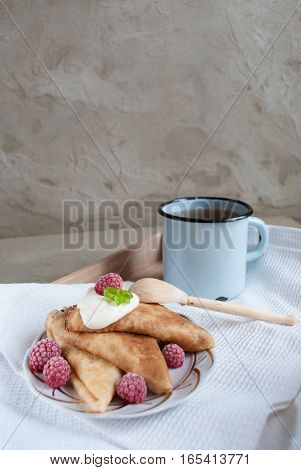 beautiful russian pancakes with sour cream, raspberry and vintage cup of tea on concrete background