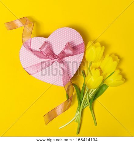 Beautiful elegant Present Gift in Heart Shape with Fresh Yellow Tulips on Yellow colorful Background. Top view. Spring Concept or Mother's Day Concept.