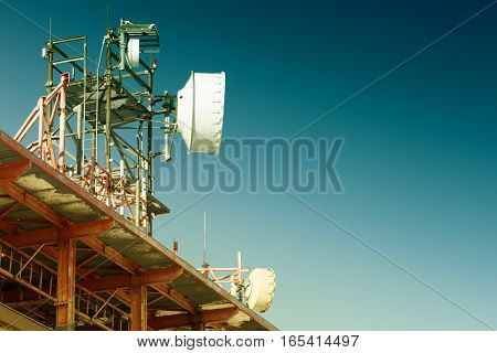 Telecommunications Tower With Several Antennas And Clear Blue Sky On Background. Filtered Image: Cro