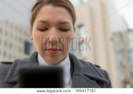 Stressed Business Woman Holding Cellphone In Hands On The City