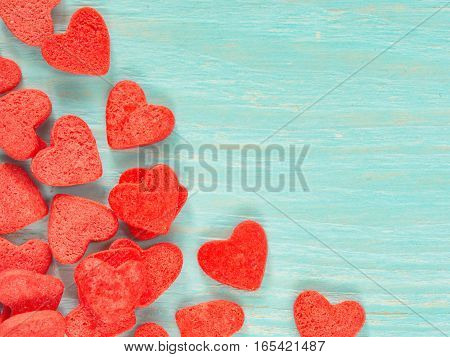 Candy heart confetti on blue wooden background. Copy space. Top view or flat lay. Close up