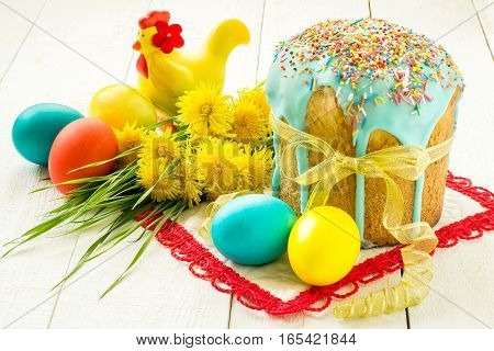 Traditional Easter treats: Easter cake and colorful easter eggs on white wooden table
