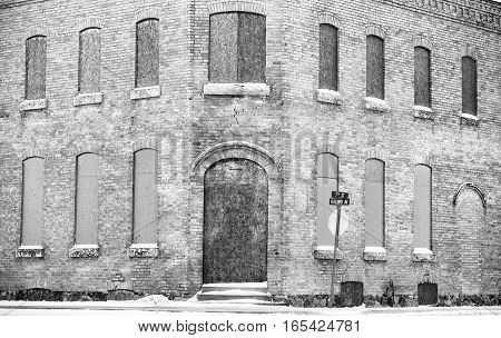 A historical two storied brick building with arched and boarded up windows in dramatic black and white