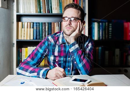 Young Man Working And Thinking In The Library