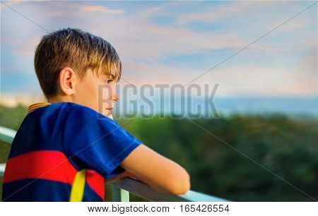 Portrait of a boy looking into the distance against the sea at sunset