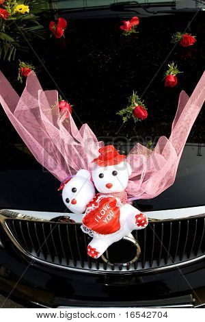 The wedding car with some flowers.
