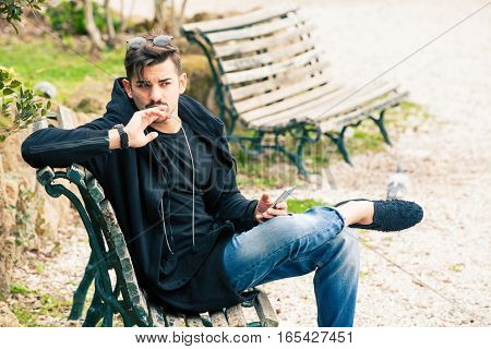 Young handsome man sitting on the bench thinking waiting with phone in hand.
