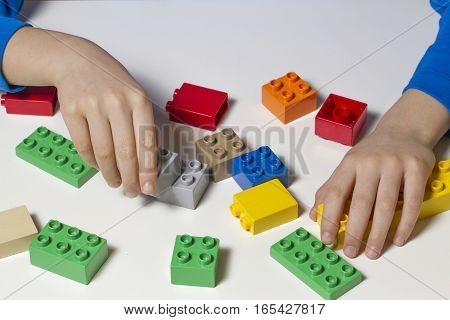 Child's hands and colorful toy building cubes. Top view. Close up