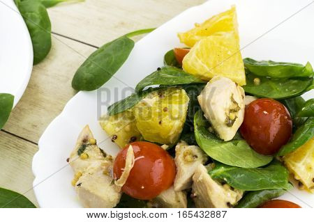 Garnished with cut feta salad from spinach, chicken, cherry tomatoes and orange on white plate