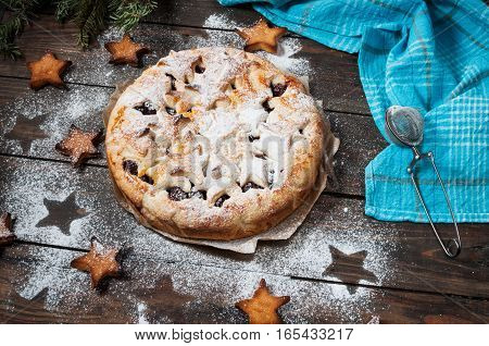 Cherry pie and star shaped cookies on rustic wooden background.